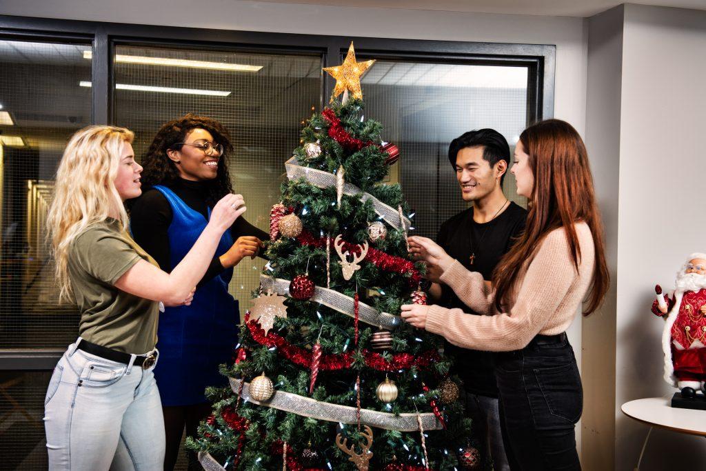 Des étudiantes décorent un arbre de Noël