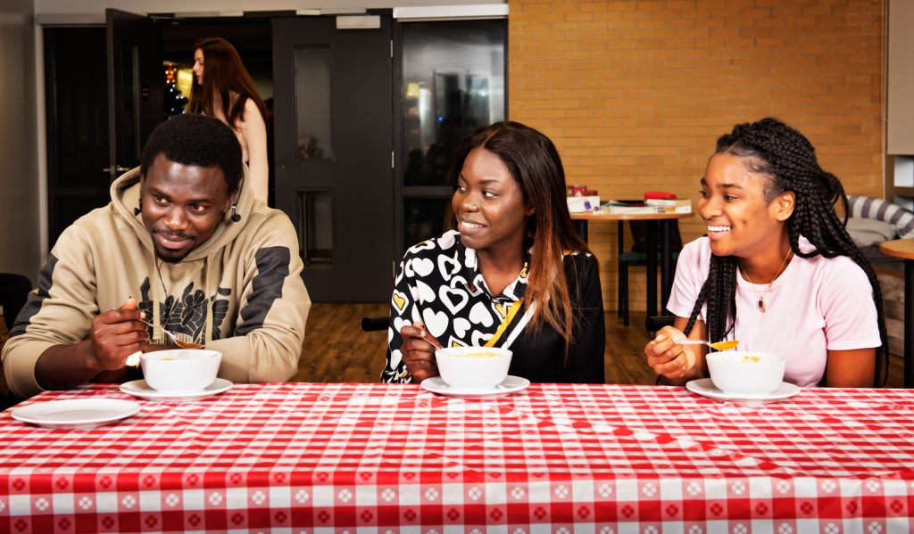 Trois étudiants prennent un repas ensemble