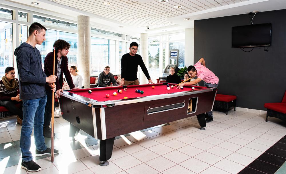 Quatre étudiants jouant au billard